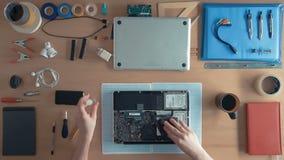 顶视图技术员工程师修理在供应和设备围拢的他的书桌上的便携式计算机 股票录像