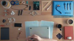 顶视图技术员工程师修理在供应和设备围拢的他的书桌上的便携式计算机 影视素材