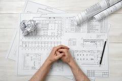 顶视图折叠了人的手木表面上的与建筑师图画 免版税图库摄影