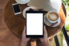 顶视图拿着有空白的白色屏幕、巧妙的电话、膝上型计算机、咖啡杯和蛋糕的手的大模型图象黑片剂个人计算机 库存照片