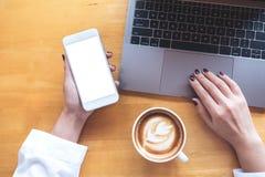 顶视图拿着有空白的白色桌面屏幕的妇女` s手的大模型图象手机,当使用有咖啡杯的时膝上型计算机 免版税库存图片