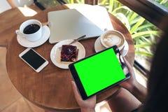 顶视图拿着有空白的绿色屏幕的手的大模型图象黑片剂个人计算机 库存照片