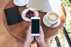 顶视图拿着有黑屏、片剂、膝上型计算机、咖啡杯和蛋糕的手的大模型图象白色智能手机在木桌上 库存照片