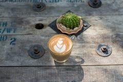 顶视图拿铁在木桌上的艺术咖啡 免版税库存图片