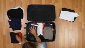 顶视图排序和包装她的衣裳的妇女的旅行概念入手提箱 股票录像