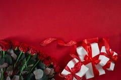 顶视图新鲜的红色玫瑰花和礼物盒在红色甲板有空的空间的设计的 对爱或情人节概念 免版税库存照片