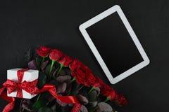 顶视图新鲜的红色玫瑰花和礼物盒在黑甲板有空的空间的设计的 对爱或情人节概念 免版税库存照片