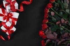 顶视图新鲜的红色玫瑰花和礼物盒在黑甲板有空的空间的设计的 对爱或情人节 免版税库存图片
