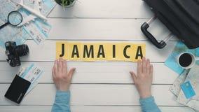 顶视图时间间隔递放置在用旅行项目装饰的白色书桌词`牙买加` 股票视频