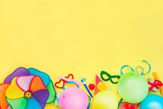 顶视图明亮的党工具和装饰- baloons,滑稽的狂欢节面具,在黄色背景的欢乐闪亮金属片 生日快乐gr 库存照片