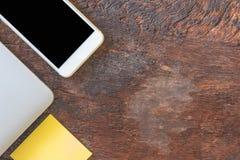 顶视图智能手机、膝上型计算机和岗位笔记或者柱子在老木背景 免版税库存照片