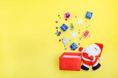 顶视图有开放惊奇箱子和飞溅datails的装饰圣诞老人外面 背景明亮的黄色 圣诞节和新 免版税库存照片