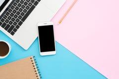 顶视图有膝上型计算机、电话、铅笔、笔记本和咖啡杯的办公桌在蓝色粉色背景 免版税库存图片