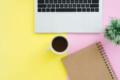 顶视图有膝上型计算机、笔记本和咖啡杯的办公桌在淡色背景 免版税库存照片