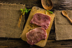 顶视图未加工的猪肉两个片断食用香料和胡椒 油和盐在老木桌上 库存照片