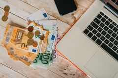 顶视图欧洲钞票和硬币和膝上型计算机的零件 免版税库存图片