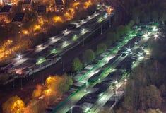 顶视图汽车车库由铁路划分了在城市的郊区,在晚上 免版税库存图片
