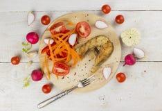 顶视图油煎了鱼用红萝卜,蕃茄,大蒜,庭院萝卜 库存图片