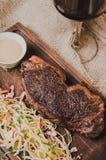 顶视图烤了ribeye牛排用炖煮的食物圆白菜和葡萄酒杯红葡萄酒、草本和香料在棕色麻袋布  免版税库存图片