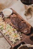 顶视图烤了ribeye牛排用炖煮的食物圆白菜和葡萄酒杯红葡萄酒、草本和香料在棕色麻袋布  免版税图库摄影