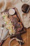 顶视图烤了ribeye牛排用炖煮的食物圆白菜和葡萄酒杯红葡萄酒、草本和香料在棕色麻袋布  免版税库存照片