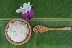 顶视图烹调了在碗的在匙子和兰花的米在绿色香蕉叶子和稻 库存照片