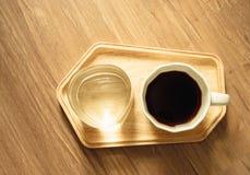 顶视图照片、一个白色杯子americano无奶咖啡和一杯在木盘子的矿泉水在棕色木纹理 库存照片