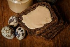 顶视图特写镜头黑麦面包切片用tahini黄油和鹌鹑蛋 库存图片