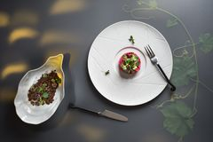 顶视图现代板材用桃红色甜菜根意大利煨饭和水芹,与乳酪快餐的黑面包在被遮蔽的背景 免版税库存照片