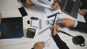顶视图男性和分析财政报告的同事的女性手在办公室 坐在桌上的企业队和 影视素材