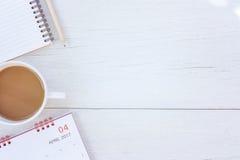 顶视图笔记本、日历和咖啡杯在白色木tabl 免版税库存图片