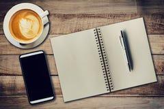 顶视图笔记本、笔、咖啡杯和电话在木桌, Vin上 免版税库存图片