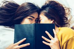 顶视图美丽的年轻亚裔妇女女同性恋的愉快的夫妇亲吻和微笑,当在家时一起在床上在书下 库存图片