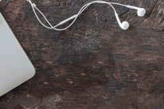 顶视图膝上型计算机和耳机在老木背景与拷贝空间 图库摄影