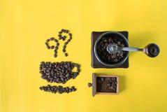 顶视图舱内甲板在黄色背景放置在杯子和气味象形状的咖啡豆和葡萄酒木磨咖啡器 库存照片