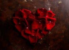 顶视图舱内甲板在黑暗的背景放置在心脏形状的红色玫瑰花瓣 拉丁文,激情概念 红色上升了 免版税库存图片