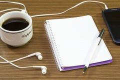 顶视图营业所书桌 笔记本,铅笔,无奶咖啡,树,手机,在木桌背景的纸夹 免版税库存照片