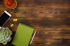 顶视图营业所书桌 笔记本,铅笔,茶杯,植物,手机,在木桌背景的纸夹 免版税图库摄影