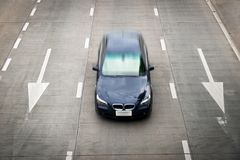 顶视图蓝色小汽车赛和在路的白色箭头标志 图库摄影