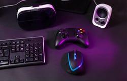 顶视图赌博齿轮,老鼠,键盘,控制杆,耳机,在黑桌背景的VR耳机 库存图片