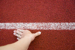 顶视图赛跑者在跑在体育体育场的开始位置轨道空白线路的人手 免版税库存图片