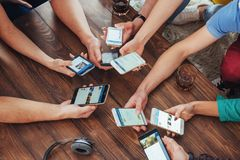 顶视图递圈子使用在咖啡馆-多种族朋友机动性的电话使上瘾的内部场面从上面- Wifi被联络的人民 免版税库存照片