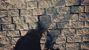 顶视图鞋子的走在历史古老边路的人POV  图库摄影