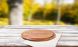 顶视图餐巾和比萨书桌在木桌上有被弄脏的公园背景,假装 免版税库存图片