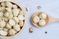 顶视图马卡达姆坚果和壳在木碗 免版税库存图片