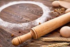 顶视图鸡蛋、面团、面粉和辗压别针在木桌上 免版税图库摄影