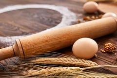 顶视图鸡蛋、面团、面粉和辗压别针在木桌上 免版税库存图片