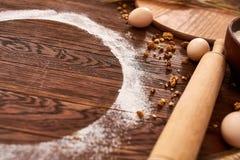 顶视图鸡蛋、面团、面粉和辗压别针在木桌上 库存图片