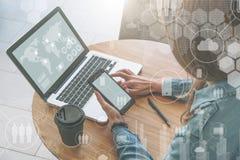 顶视图,一个黑屏智能手机的特写镜头在网上学会少妇的手上坐在圆的木桌上和 免版税库存图片