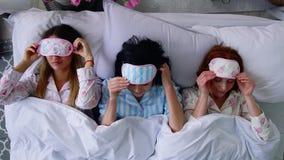 顶视图,三个美丽的女孩在床上去睡觉和投入眼睛绷带睡觉 股票视频